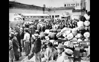 Mar. 21, 1942: The first contingent of 86 Japanese waits to board three buses and a truck at Maryknoll School playground at Third and Hewitt Sts. to travel to Manzanar. About 200 additional friends and family came to say goodbye. This photo was published on the front page of the Mar. 22, 1942 LA Times.
