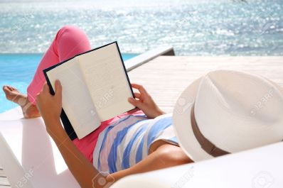 24761864-Woman-reading-book-relaxed-in-deck-chair-Stock-Photo